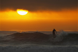 A Surfer Rides His Last Wave into Shore as the Sun Sets into an Incoming Layer of Fog in Cardiff