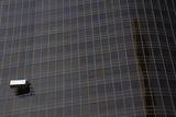 A Window Cleaner Works from a Platform Hanging from the Side of a Building in Central Beijing