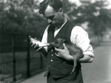 Keeper Harry Warwick Bottle Feeds a Baby Warthog at London Zoo  in August 1922