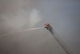 A Firefighter Battles a Fire from the Top of a Ladder Truck