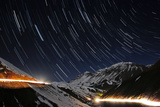 A Time-Exposure of Star Trails Above a Road with Headlights in the Snowy Alborz Mountains