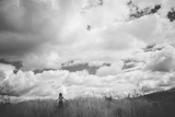 Young Girl Standing in a Field with Clouds