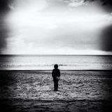 Female Figure Standing Alone on Beach Papier Photo par Rory Garforth