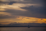 A Sailboat Drifts in the Puget Sound as the Olympic Mountains are Silhouetted Against an Orange Sky