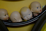 Four Doll's Heads in a Row in an Antique Shop