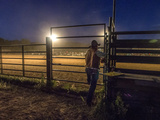 A Rodeo Performer Watches the Rodeo Action from Outside a Fence