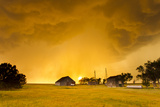 Orange Illuminated Sky as Sun Sets Behind a Supercell Thunderstorm and Shines Through a Rain Shaft