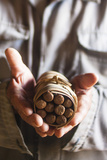 A Tobacco Grower Holds a Bundle of Cigars Hand-Rolled from the Tobacco Growing in His Shed