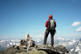A Climber Stands at the Summit of a Mountain Overlooking the Mountains of Glacier National Park