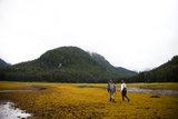 A Man and Woman Walk Along the Tidal Area of an Inlet in Remote Alaska