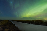 Green Aurora and Starry Sky Above a Stream Running Through Farm Lands in Southern Iceland
