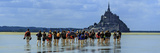Tourists Walk the Sea Floor at Low Tide to the World Heritage Site Mont Saint Michel Monastery