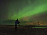 A Photographer Shooting a Green Aurora Above Farm Lands in Southern Iceland
