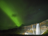 Green Aurora Shines Through Clouds Above Seljalandsfoss  a Waterfall in Southern Iceland