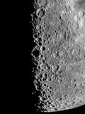 The Moon Seen Through a Telescope with Numerous Craters Along the Lunar Terminator