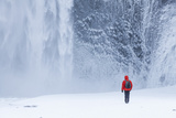 One Person in Red Jacket Walking in the Snow Towards Skogafoss Waterfall in Winter