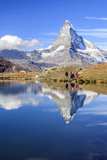 Hikers Walking on the Path Beside the Stellisee with the Matterhorn Reflected