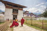 Two Monks Dressed in Traditional Red Access the Punakha Dzong  Punakha