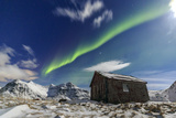 Northern Lights (Aurora Borealis) over a Small Wooden House Flakstad