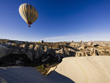 Hot Air Balloons Flying Among Rock Formations at Sunrise in the Red Valley