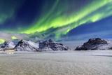 Northern Lights (Aurora Borealis) Illuminate the Sky and the Snowy Peaks