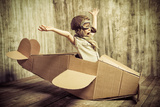 Cute Dreamer Boy Playing with a Cardboard Airplane Childhood Fantasy  Imagination Retro Style