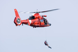 A Rescue Swimmer Is Lowered from a US Coast Guard Hh-65 Dolphin Helicopter