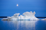 Canada  Nunavut  Moon Rises Behind Melting Iceberg in Frozen Channel