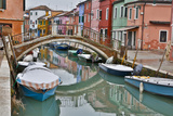 Boats Docked Along Canal with the Colorful Homes of Burano  Italy