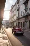 Vintage Cars Drive Down a Street in Havana