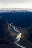 A Winding River Snakes its Way Through a Highland Tundra Valley Between Steep Mountains