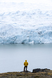 A Hiker Dwarfed by the Fracture Zone of a Glacier on the Greenland Ice Sheet