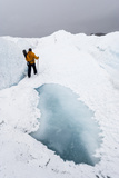 A Hiker Passing Between a Dangerous Crevasse and a Melt Pond on the Greenland Ice Shelf
