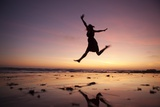 A Woman Jumping on the Beach at Sunset