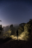 A Hiker Walks Down a Trail under the Stars