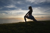 A Woman Stretching in a Meadow Above the Pacific Ocean at Sunset