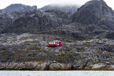 A Bright Red Cottage on the Rugged and Brutal Rock Shoreline of a Fjord