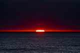 A Slither of Sunlight Pierces a Storm Cloud Above a Darkened Ocean at Sunset