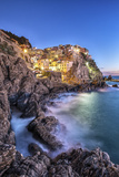 Manarola Village Illuminated by the Blue Light of Dusk with its Typical Pastel Colored Houses