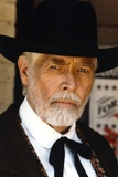 James Coburn Portrait in Black Suit and White Shirt with Black Collar Ribbon and Brimmed Hat