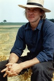 Alexander Godunov sitting on a Hay Stack wearing Blue Long Sleeves and a Hat