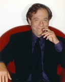 George Segal smiling While Siting on Red Couch in Black Suit and Necktie