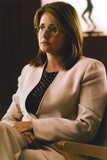Lorraine Bracco sitting in White Blazer with Printed Blouse Under
