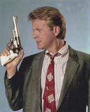 David Rasche Holding a Pistol in Black Suit with Red Tie
