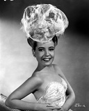 Gloria DeHaven smiling in A Portrait wearing A Feather Hat