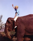 Jay North Riding on Elephant in Blue Short Sleeve Shirt with Right Hand Raised Up Waving