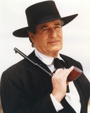 Hugh O'Brien wearing a Black Suit and Hat with Pistol