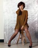 Kim Delaney sitting on Chair in Brown Dress