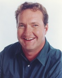 Randy Quaid smiling wearing Blue Polo Portrait with White Background