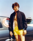 Patrick Duffy standing in Swimming Trunks with Black Jacket
